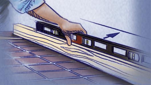 Utilice una regla de nivelar o un enrasador de 2 x 4 y un nivelador para encontrar el punto más elevado del piso.